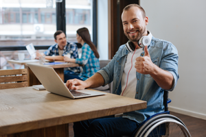 Man in wheelchair at a table, looking at a laptop and giving the thumbs up sign.