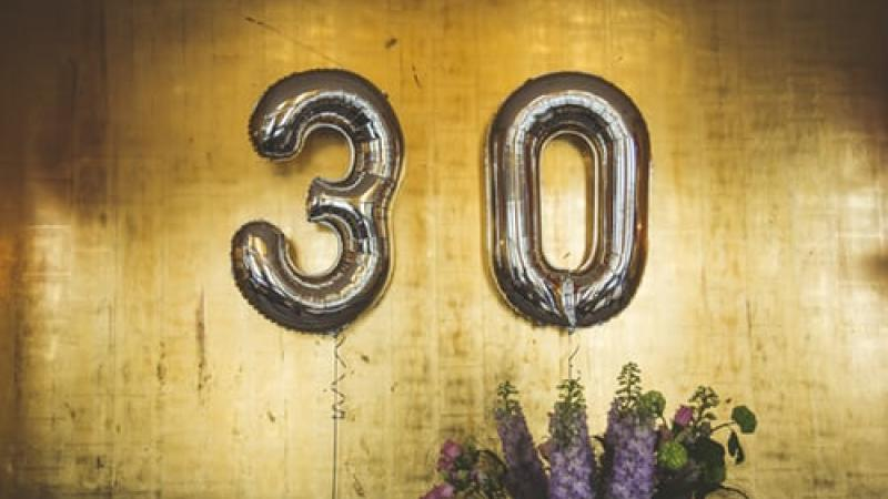 Silver number balloons that say 30 against a gold background.