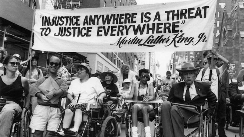 "Disabled protesters underneath a banner that reads ""Injustice anywhere is a threat to justice everywhere."""