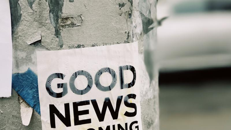 "A sign on a street pole that reads, ""good news is coming."""