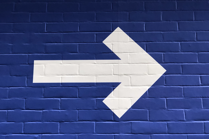 White arrow painted on blue brick wall.