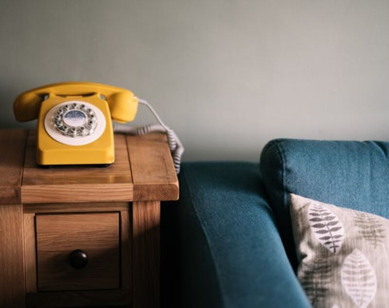 A yellow rotary phone on a table next to a blue sofa.