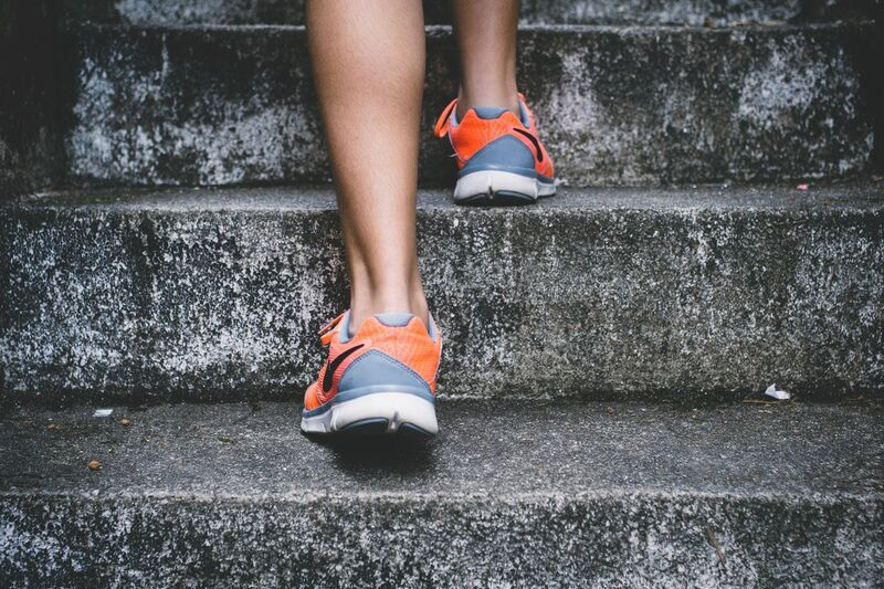 A close-up photo of a person's orange shoes as he ascends rough concrete stairs.