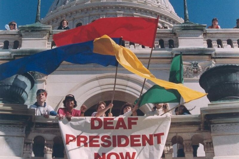 "Several people in front of a white building with colorful flags and a sign reading ""Deaf President Now"""