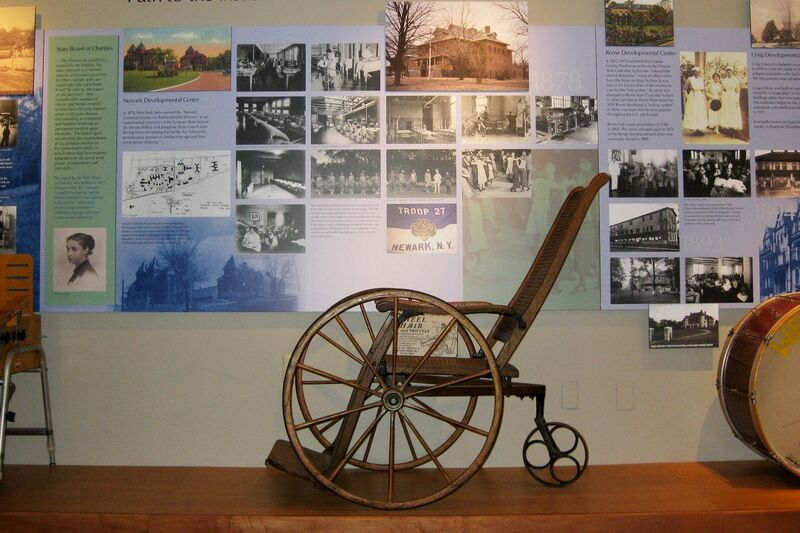 Old wooden wheelchair on display.