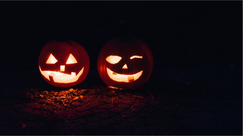 Two lighted jack-o-lanterns during night time.