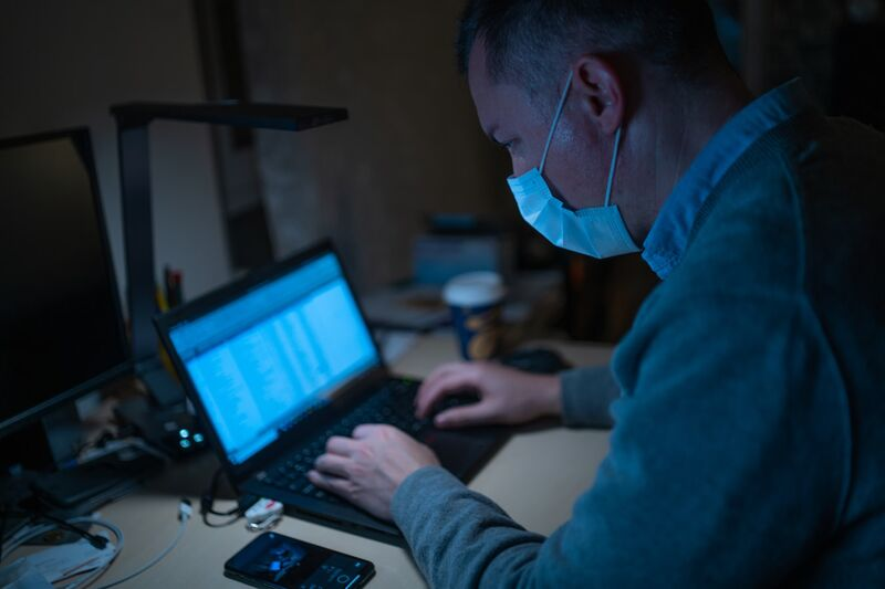 Man with a surgical mask on using laptop.