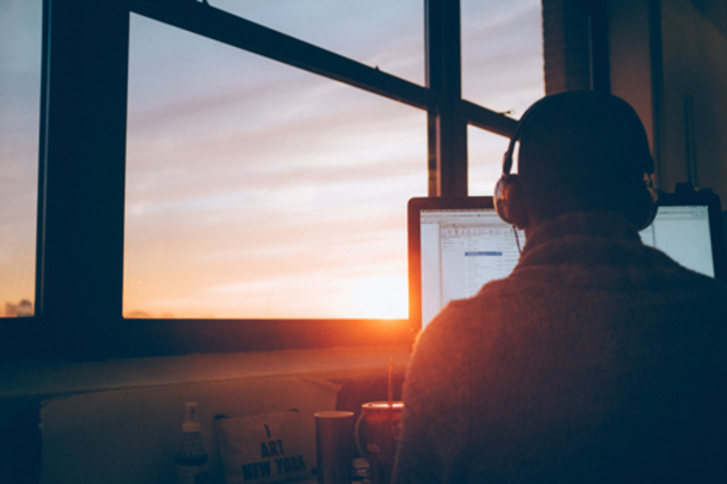 A person sitting at a computer with headphones on overlooking sunset through a window.