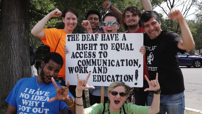 Group of people holding a sign that says THE DEAF HAVE A RIGHT TO EQUAL ACCESS TO COMMUNICATION WORK AND EDUCATION!