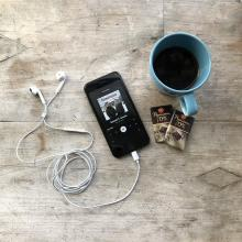 Smartphone with headphones, two chocolate bars and a cup of coffee.
