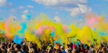 Crowd of people under a blue sky with yellow, blue, and pink colors above them