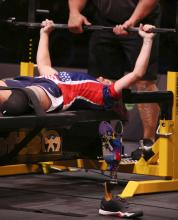 A below the knee amputee is competing in  power lifting bench press, with a spotter ensuring safety and the prosthetic lower limb off the leg, standing by itself in the foreground.