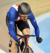 Photo of Chris Murphy wearing a Team USA speedsuit slowly winding up speed at the top of a velodrome racing track.