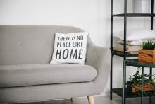 "A pillow on a couch that reads, ""There is no place like home."""