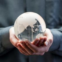 Person holding a glass globe in hands.