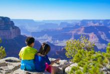 A brother and sister in colorful clothes enjoy the beautiful view of the Grand Canyon.