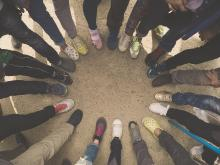 A circle is formed from a group of people all putting a foot down standing next to one another. Only the lower leg and shoes are pictured.
