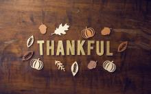 "The word ""Thankful"" in gold lettering circled by fall leaves."