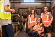 Workers in a brewery wearing safety vests having a discussion